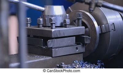 mechanics working on the milling machine hand checks item on milling machine, creating a swarf