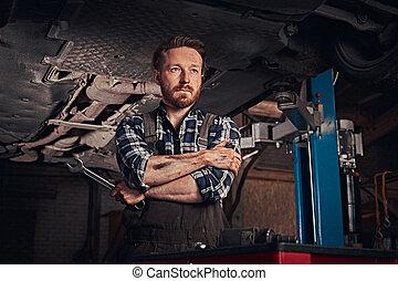 mechaniker, überquerte hände, während, stehende , unter, heben, auto, in, a, reparatur, garage.