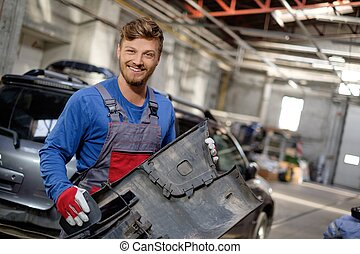 mechaniker, mit, stoßstange, in, a, werkstatt