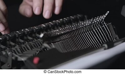 Mechanism of a retro typewriter, fingers print text. Close...