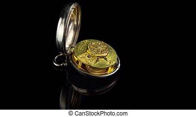 Mechanism vintage pocket watch. Black background. Time lapse...