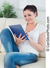 medan, couch, användande, skrivblock persondator, kvinna sitta