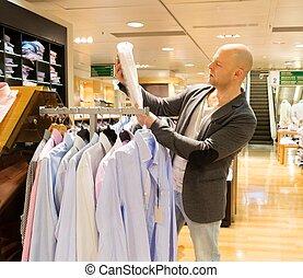 medelålderst, man, välja, shirts, in, a, köpcenter