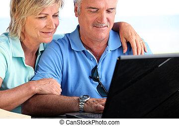 medelålderst, par, användande laptop, dator