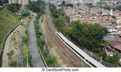 Medellin public transport metro train passing by a drone