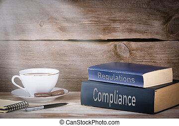 medgørlighed, og, regulations., stakk af bøger, på, træagtigt skrivebord