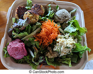 Medi Bowl - Kalo falafel, smokey baba ganoush, beet hummus, refreshing millet tabouleh over bed of greens drizzled with special tahini sauce in paper tray on flower table clothe.