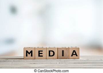 Media sign on a wooden table
