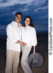 mediados de-adulto, pareja hispana, sonriente, en, playa, en, amanecer