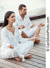 Mediating together. Top view of beautiful young couple in white clothing meditating outdoors together and keeping eyes closed
