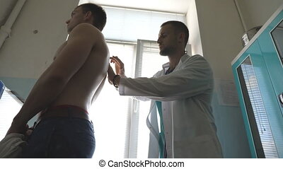 Medic checking back of guy in her office at the hospital. Doctor examining young male patient with stethoscope. Medical worker listening heartbeat of athletic man. Close up