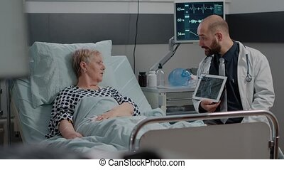Medic explaining radiography diagnosis on tablet to patient with disease. Doctor showing x ray scan on device for healthcare of retired woman with IV drip bag and nasal oxygen tube.