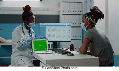 Medic holding horizontal green screen on modern tablet. Doctor showing technology on digital device with mockup template and chroma key for isolated background to patient with face masks