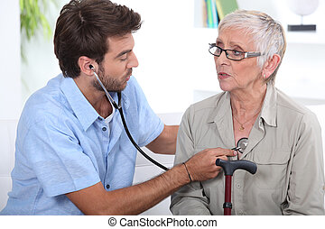 Medic listening to a senior woman's chest