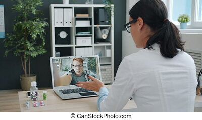 Medic young woman in uniform is talking to sick man online using computer from clinic office discussing pills and prescribing treatment in internet.