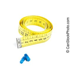 medical blue pills in front of measure tape, concept for diet