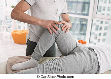 Nice professional doctor touching his patients knee