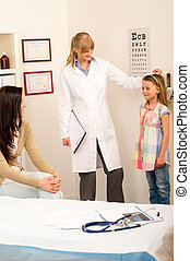 Medical check-up at pediatrist girl measure height
