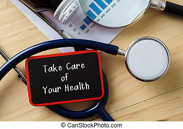 Medical conceptual.Stethoscope on wooden table with word TAKE CARE OF YOUR HEALTH.