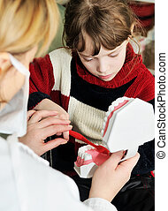 Medical. Dentist training a little girl to clean a teeth - ...