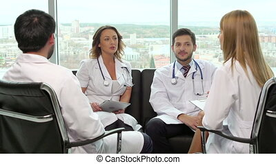 Medical Department Meeting - Four medical workers sitting in...