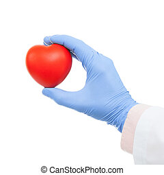 Medical doctor holding heart shaped toy in hand - studio shot