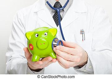 Medical doctor holding stethoscope and piggybank in hand - studio shot