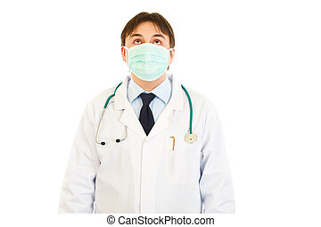 Medical doctor in mask looking up  isolated on white