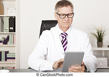 Medical Doctor Reading Reports Using Tablet