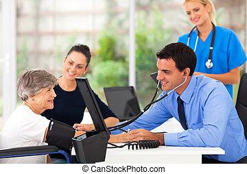 medical doctor taking senior woman's blood pressure