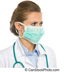 Medical doctor woman in mask looking on copy space