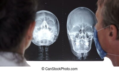 Over the shoulder shot of two medical doctors or health car workers having a discussion about a cranial x-ray of a patient.