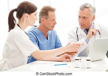 Medical doctors team using computer. Medical doctors team...