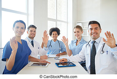 happy doctors meeting and waving hands at hospital