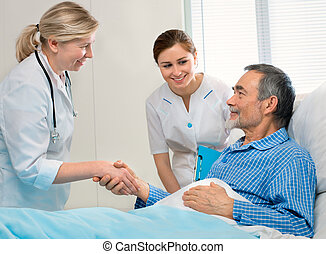 medical exam - doctor shakes hands with patient in hospital ...