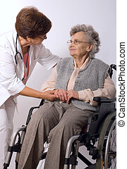 female doctor examining wrist of senior patient at home