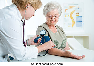 Medical exam - Female doctor measuring blood pressure of...