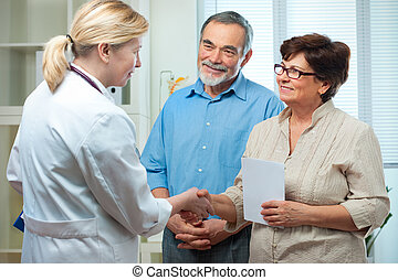 medical exam - senior couple visiting a doctor