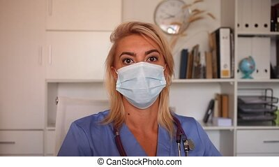 Medical female worker enters patient data into laptop