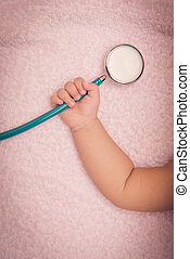 medical instruments stethoscope in hand of baby girl