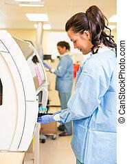 Medical Lab Tech Loading Coagulation Test - Side view of...