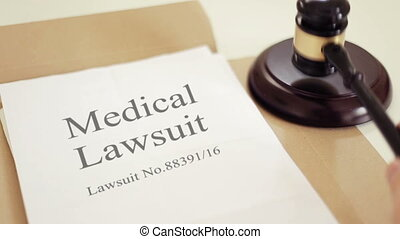 Medical lawsuit documents with gavel placed on desk of judge in court