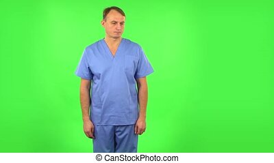 Medical man in anticipation of worries, then guilty hides his eyes. Handsome man dressed in blue medical uniform on a green screen in the studio