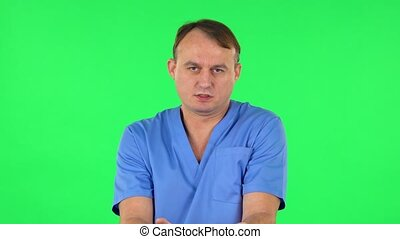 Medical man strictly gesturing with hands shape meaning denial saying NO. Green screen