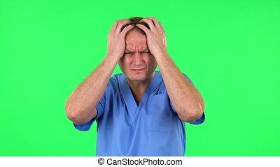 Medical man suffering from headache from fatigue. Green screen