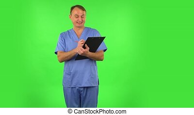 Medical man thinks, speaks and writes at black folder with pensil. Green screen