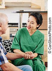 Medical nurse holding hand of senior patient