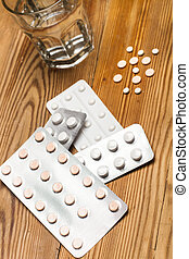 Medical pills and pill blisters with a glass of water
