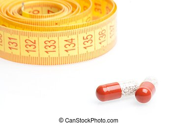 medical pills for dieting in front of measuring tape
