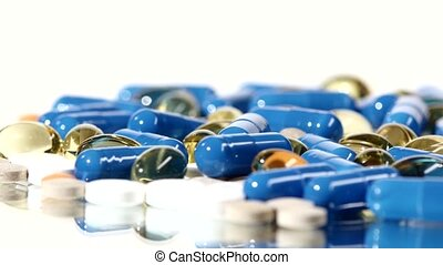 Medical pills, tablets and capsules, rotation, reflection, close up, on white